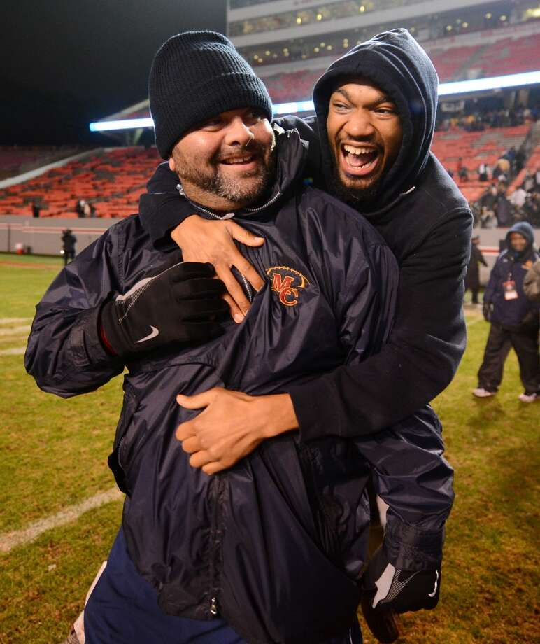 Charlotte Mallard Creek head coach Michael Palmieri is given a congratulatory hug following his team's 59-21 victory over Wake Forest in the North Carolina Class 4-AA High School Championship football game in Raleigh, N.C., on Saturday, Dec. 14, 2013. (AP Photo/The Charlotte Observer, Jeff Siner) MAGS OUT; TV OUT; NEWSPAPER INTERNET ONLY Photo: Jeff Siner, Associated Press
