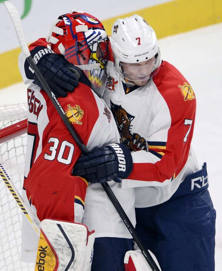 Florida Panthers goalie Scott Clemmensen (30) gets a hug from teammate Dmitry Kulikov after defeating the Montreal Canadiens in NHL action Sunday, Dec. 15, 2013 in Montreal.  (AP Photo/The Canadian Press, Ryan Remiorz) Photo: Ryan Remiorz, Associated Press