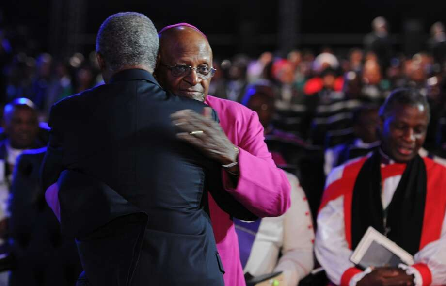 Archbishop Desmond Tutu is hugged as he arrives for the funeral service for former South African President Nelson Mandela in Qunu, South Africa, Sunday, Dec. 15, 2013. (AP Photo/Felix Dlangamandla, Pool) Photo: Felix Dlangamandla, Associated Press