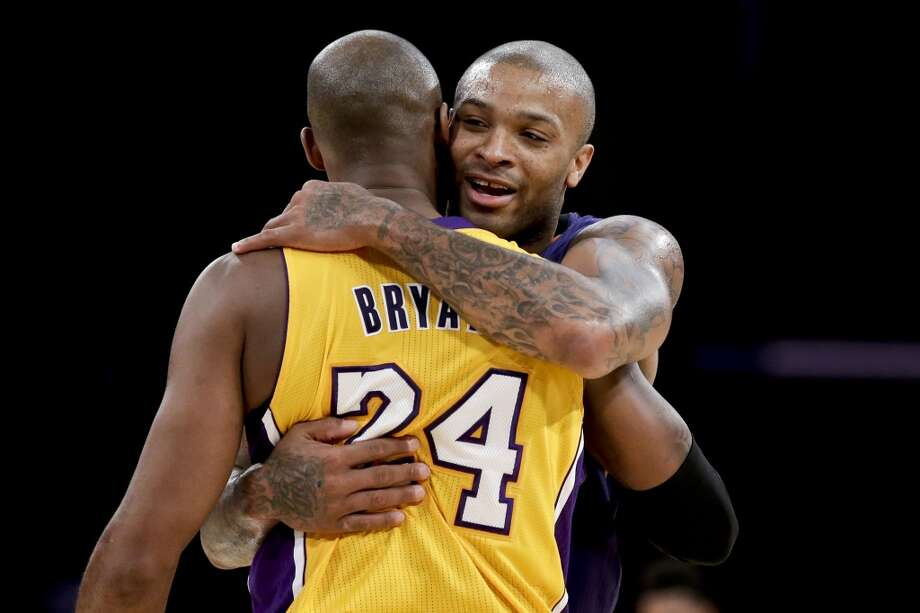 Phoenix Suns forward P.J. Tucker, right, hugs Los Angeles Lakers guard Kobe Bryant after an NBA basketball game in Los Angeles, Tuesday, Dec. 10, 2013. (AP Photo/Chris Carlson) Photo: Chris Carlson, Associated Press