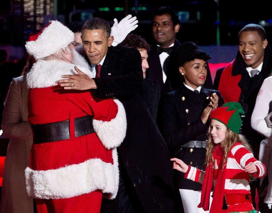 US President Barack Obama (2nd L) hugs Santa Claus after lighting the National Christmas Tree on the Ellipse near the White House in Washington on December 6, 2013.   AFP PHOTO/Nicholas KAMMNICHOLAS KAMM/AFP/Getty Images Photo: NICHOLAS KAMM, AFP/Getty Images