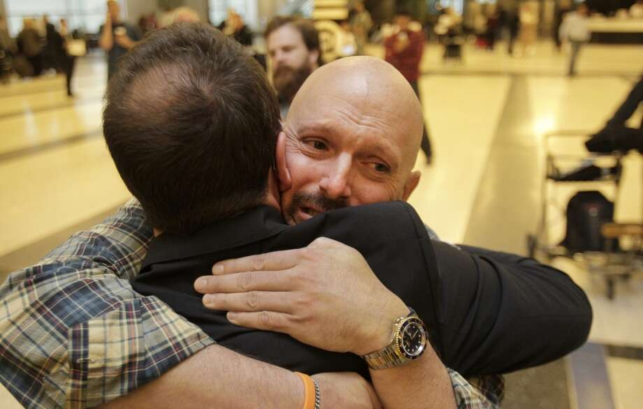Larry Wilson, right, a leukemia survivor, hugs his bone-marrow donor, Johann Beissal, left, for the first time after Johann arrived at Bush Intercontinental Airport from Germany, Friday, Nov. 22, 2013, in Houston. ( Melissa Phillip / Houston Chronicle ) Photo: Melissa Phillip, Houston Chronicle