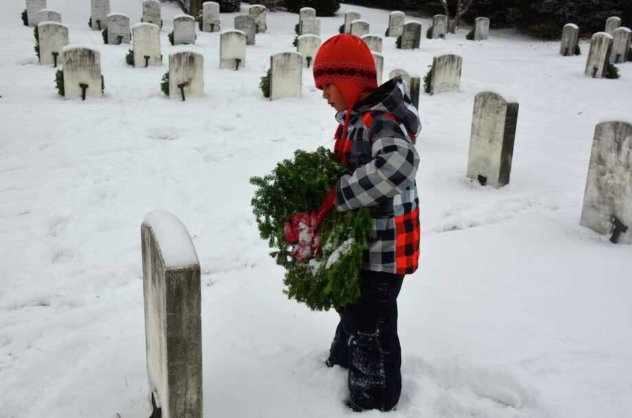 Nine-year-old Jack Grayeb reads the name of the fallen soldier before laying down his wreath on gravestone during the Wreaths Across America event held at the Spring Groves Veterans Cemetery in Darien, Conn., on Saturday, Dec. 14, 2013. Photo: Jeanna Petersen Shepard / Darien News freelance Jeanna Petersen Shepard