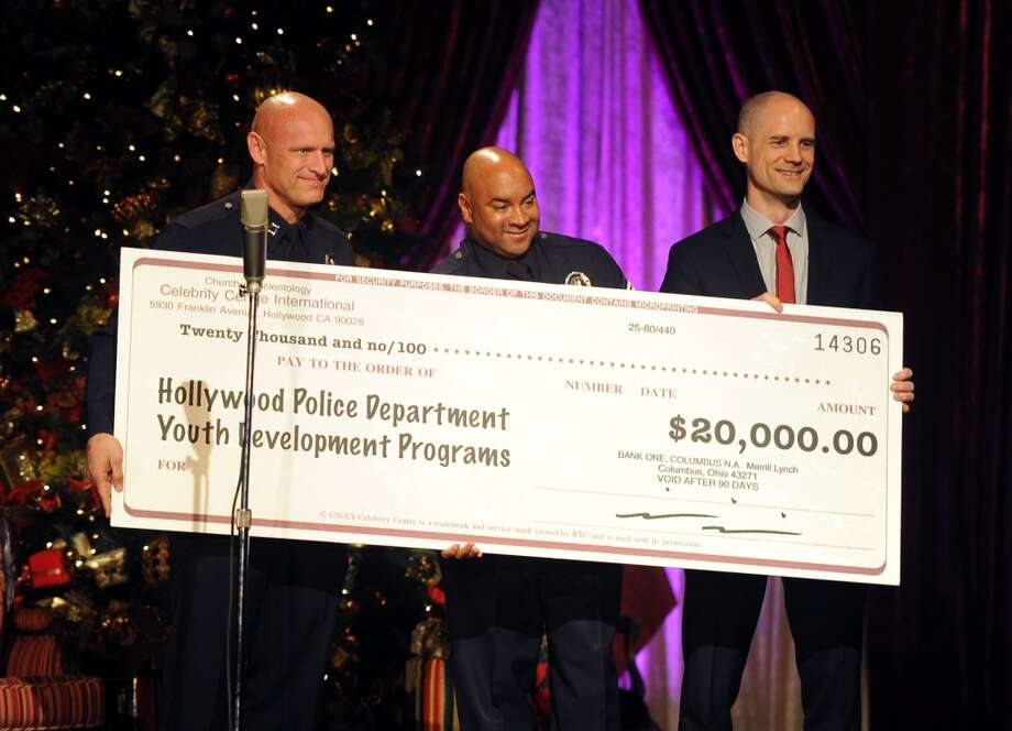"LAPD Hollywood Division Area Commander Peter Zarcone, Sgt. Darrell Davis, and Church of Scientology Celebrity Centre Vice President Greg LaClaire with the check presentation onstage during the Church of Scientology Celebrity Centre's 21st ""Christmas Stories"" at the Church of Scientology Celebrity Centre on December 14, 2013 in Los Angeles, California. ""Christmas Stories"" benefits the Hollywood Police Department's Youth Development Programs for underprivileged children. Photo: Kevin Winter, Getty Images"