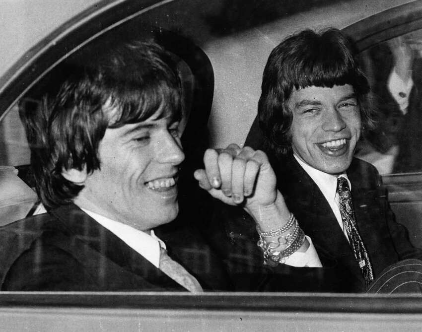 10th May 1967: Rolling Stones songwriters, guitarist Keith Richards, left, and singer Mick Jagger share a joke in the back of a car as they leave Chichester Magistrates Court where they appeared on drug summonses.