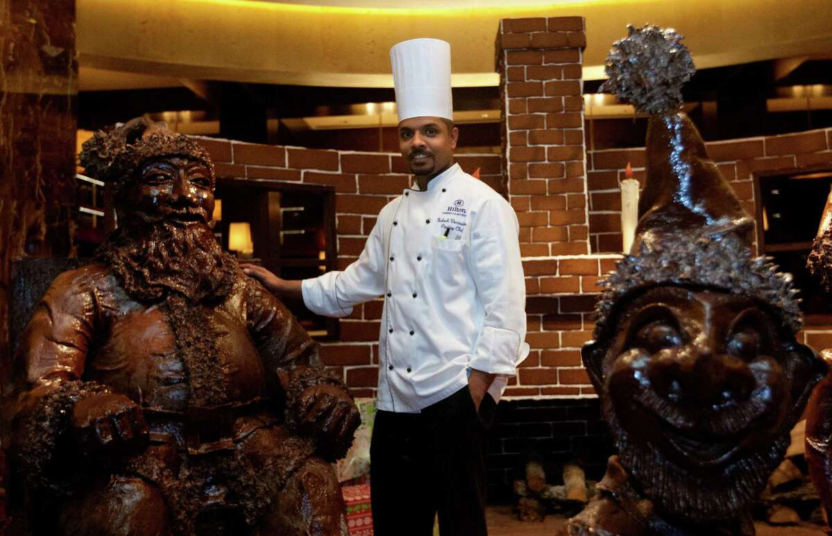 Award-winning Pastry Chef Mahesh Weerasinghe stands amongst his hand-sculptured, chocolate art at the Hilton Americas in downtown, Monday, Dec. 16, 2013, in Houston. Chef Mahesh, along with the culinary and property operations teams, created a 1000-pound Santa in his chair, accompanied by his elves and a wagon full of toys, all made from dark chocolate. The non-edible chocolate, after it was coated with a preserve, took over 400 man hours and two months of work to create.