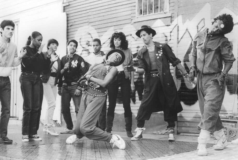 "A crowd gathers as street dancer Turbo (Michael ""Shrimp"" Chambers, center) ""gets down with his moves"" as dancing partner Ozone (Adolfo ""Shabba-Doo"" Quinones, second right) cheers him on in ""Breakin',"" 1984. Photo: Cannon Films"