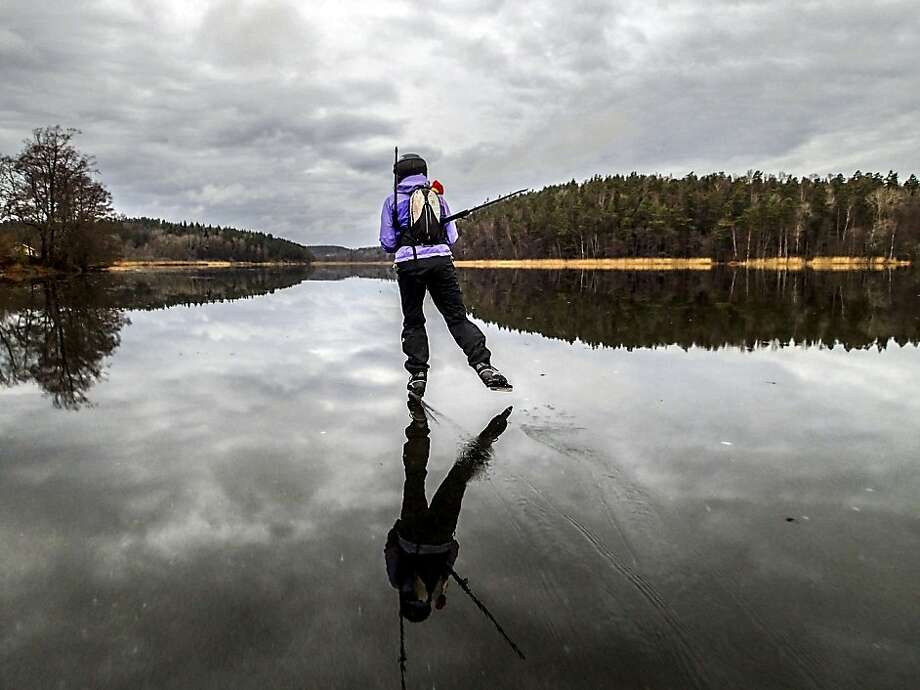 A skater glides across the water on Lake Orlangen, south of Stockholm. Very clear ice underneath a thin layer of water 