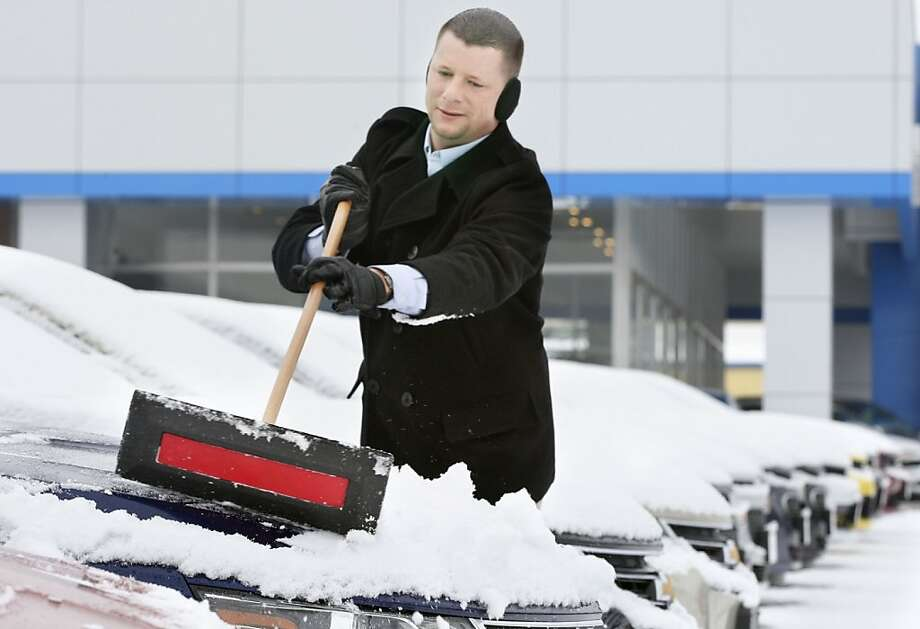 Virginia is for snow lovers: Sales consultant Mike Whitacre clears snow from new cars for the third time in a week at Jim Stutzman Chevrolet-Cadillac in Winchester, Va. Photo: Scott Mason, Associated Press