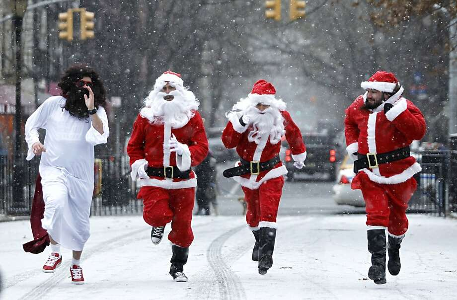 Not suited for this weather: Santa Clauses running in New York's annual SantaCon bar crawl are joined by a bearded elf who's out of uniform. Photo: Kena Betancur, Getty Images