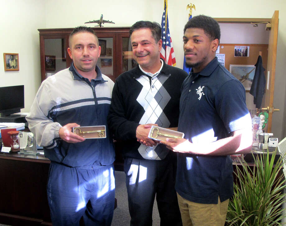 Ansonia Mayor David Cassetti presents the key to the city to Ansonia High School football coach Tom Brockett, left, and star running back Arkeel Newsome, right, at City Hall in Ansonia, Conn. on Monday, Dec. 16, 2013. Photo: Michael P. Mayko / Connecticut Post