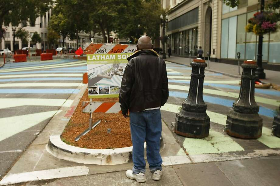 """Walter Adams, 76, who was born and raised in Oakland, inspects the sign detailing the plans for Latham Square. The square is at the intersection of Broadway and Telegraph, and it is being made into a pedestrian plaza where people can congregate and relax. It is scheduled to open on Friday, August 16. Wednesday, August 07, 2013 in Oakland, Calif. """"I've seen things change since I was born, that used to be a leather store on the corner right there,' said Adams, """"I didn't know this was going to be here till I read the sign today.' Photo: Rohan Smith, The Chronicle"""