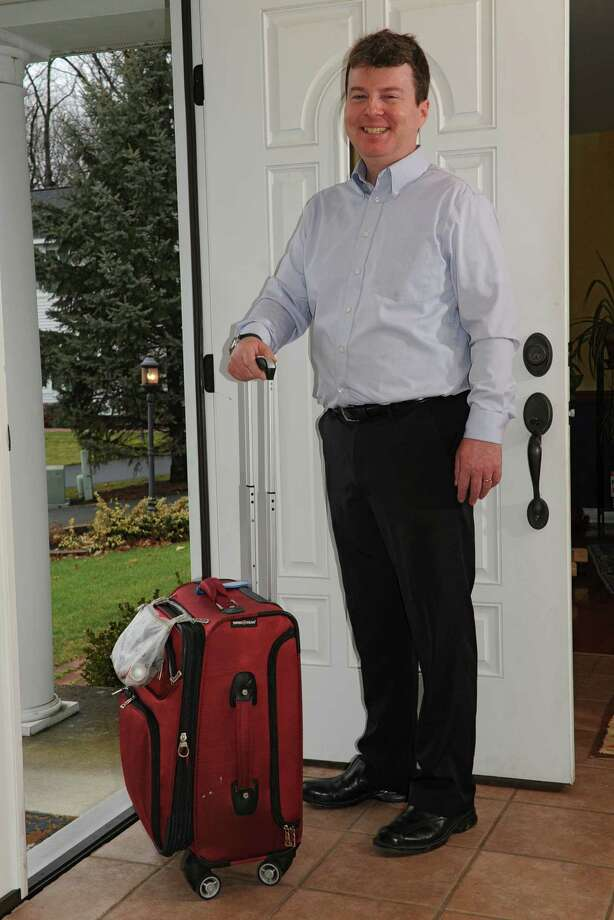 Seasoned traveler Tom Riendeau stands with his luggage at his home on Friday, Dec. 6, 2013 in Rexford, N.Y.  (Lori Van Buren / Times Union) Photo: Lori Van Buren / 00024902A