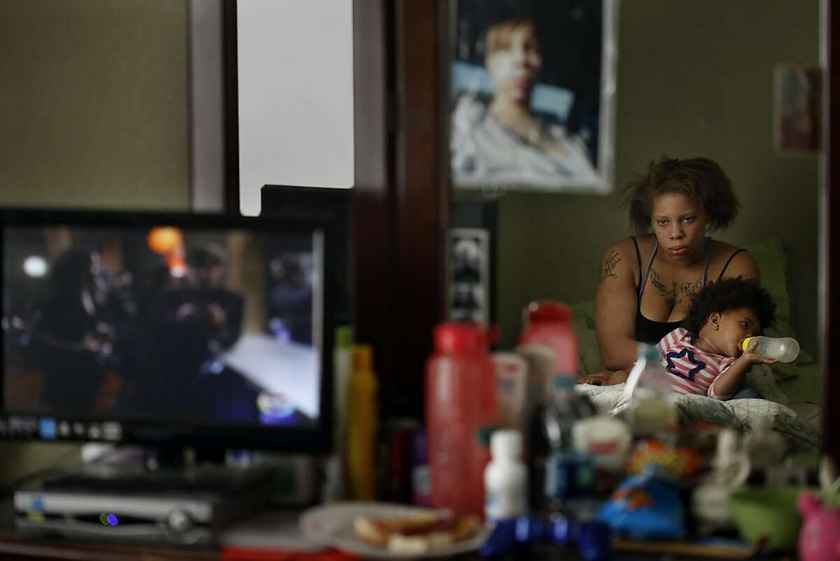 Brijjanna Price watches television while holding her daughter after having a fight with her boyfriend Quindell Anderson on Wednesday, November 6, 2013, in Hayward, Calif. Photo: Lacy Atkins, The Chronicle
