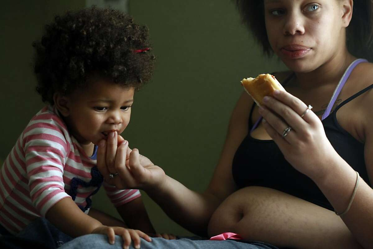 Brijjanna Price gives her daughter LaMya Deshana Price a bite of her lunch as they watch television, Wednesday, November 6, 2013, in Hayward, Calif. Photo: Lacy Atkins, The Chronicle