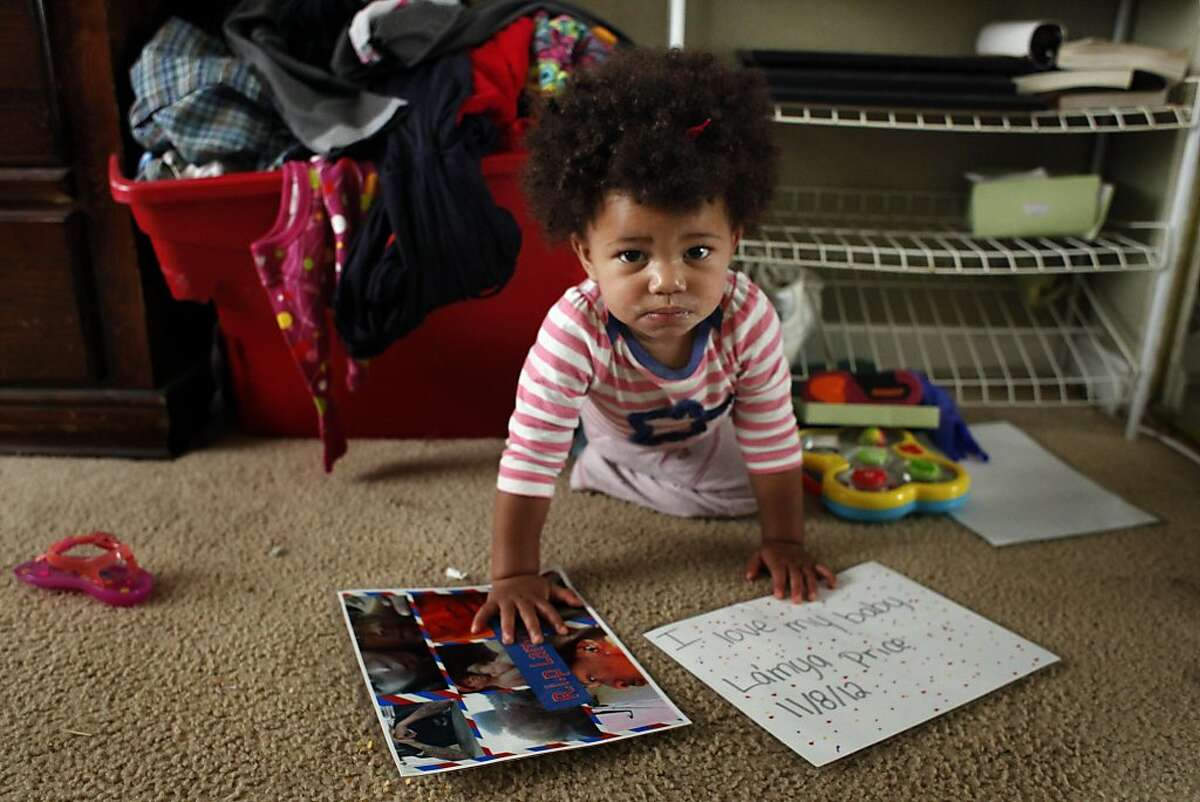 As LaMya Deshana Price crawls along the floor of the bedroom she   shares with her mother, she pulls down a collage of pictures of her uncle Lamont DeShawn Price on Wednesday, November 6, 2013, in Hayward, Calif. LaMya's mother Brijjanna Price named her after Lamont who, was one of the 131 people killed in Oakland in 2012. Photo: Lacy Atkins, The Chronicle