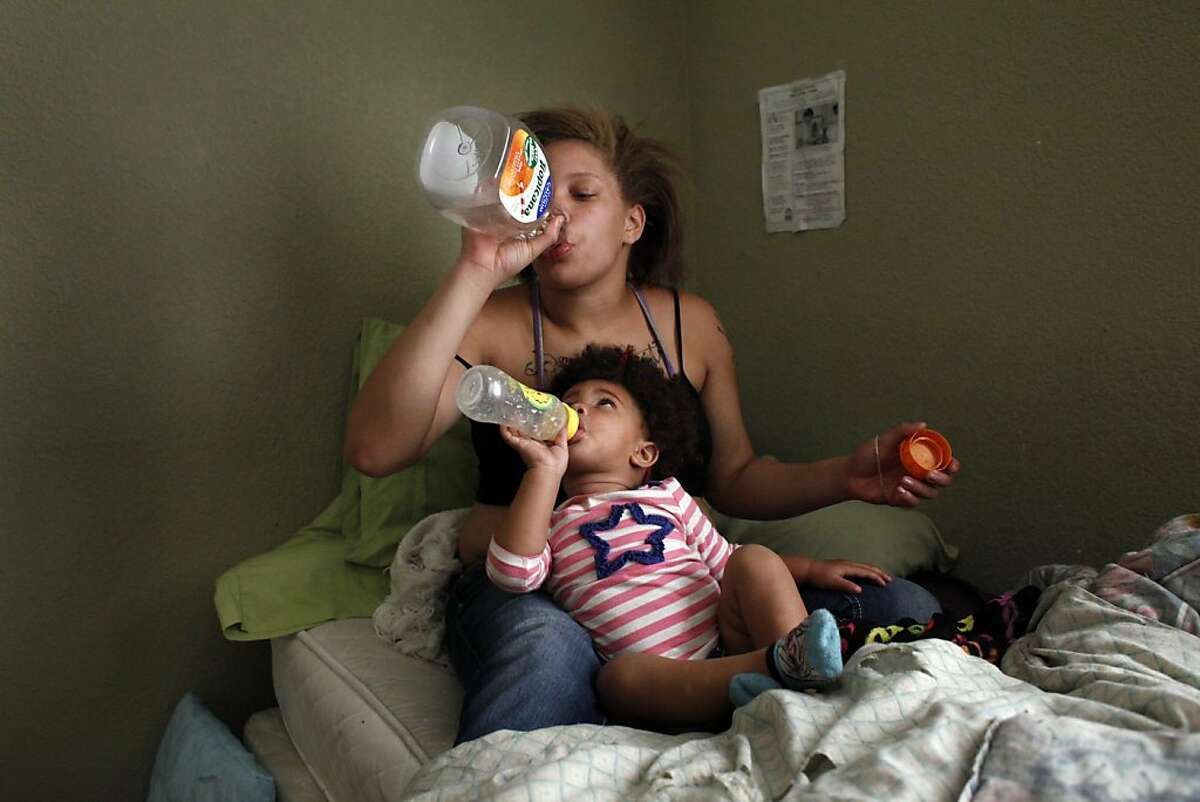 Brijjanna Price and her daughter LaMya Deshana both drink  juice while they watch television on Wednesday, November 6, 2013, in Hayward, Calif. Photo: Lacy Atkins, The Chronicle
