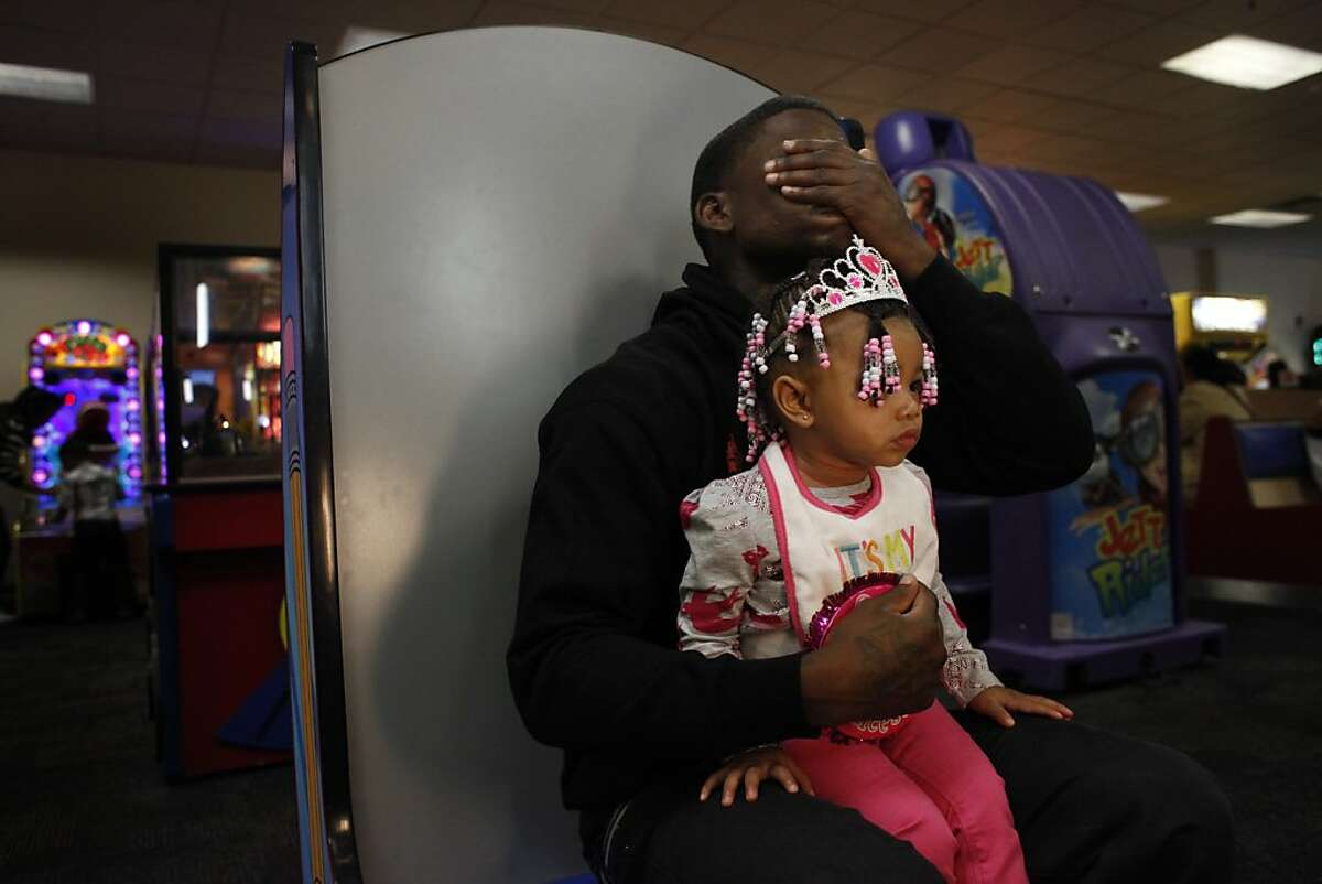 Quindell Anderson covers his eyes with his hand while reading game instructions for the photo booth while holding his daughter LaMya Deshana Price, 1, at Chuck E. Cheese's during her birthday party, Saturday, November 9, 2013, in Hayward, Calif. Photo: Lacy Atkins, The Chronicle