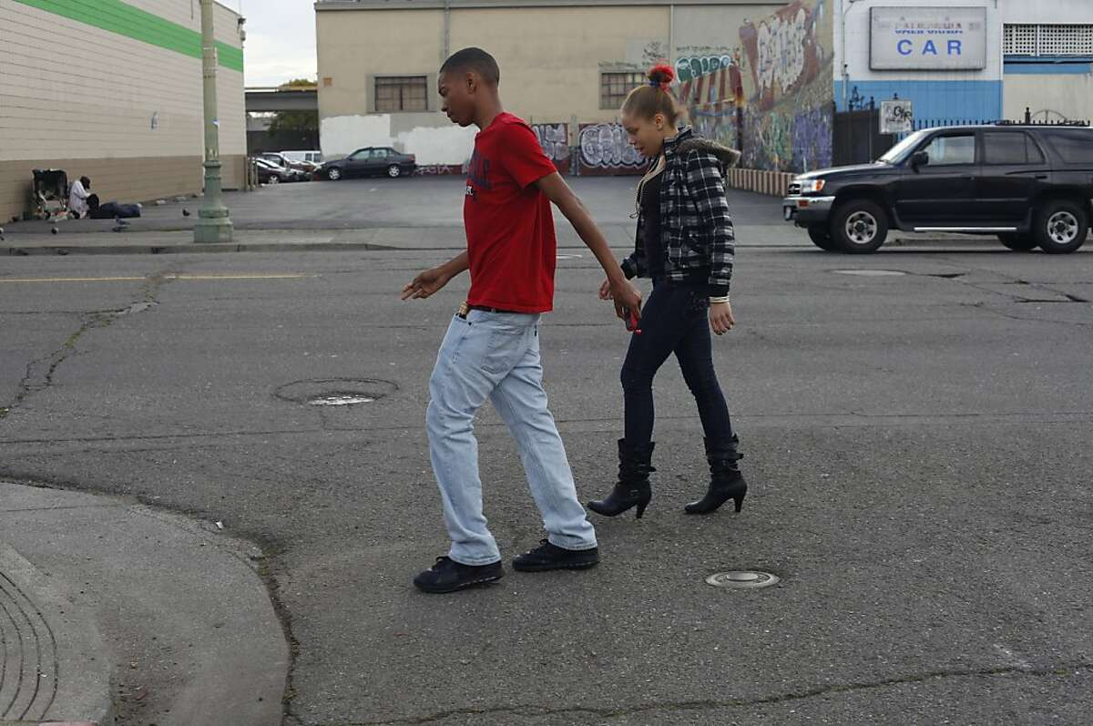 "Brijjanna Price,16, walks with her older brother Ramon Price Jr. 18, through the neighborhood known as the ""The Murder Dubbs,"" two weeks after their brother, Lamont, 17, was killed, in February 2012, in Oakland, Calif. Within those two weeks, both were shot at during a drive by in the streets. Photo: Lacy Atkins, The Chronicle"