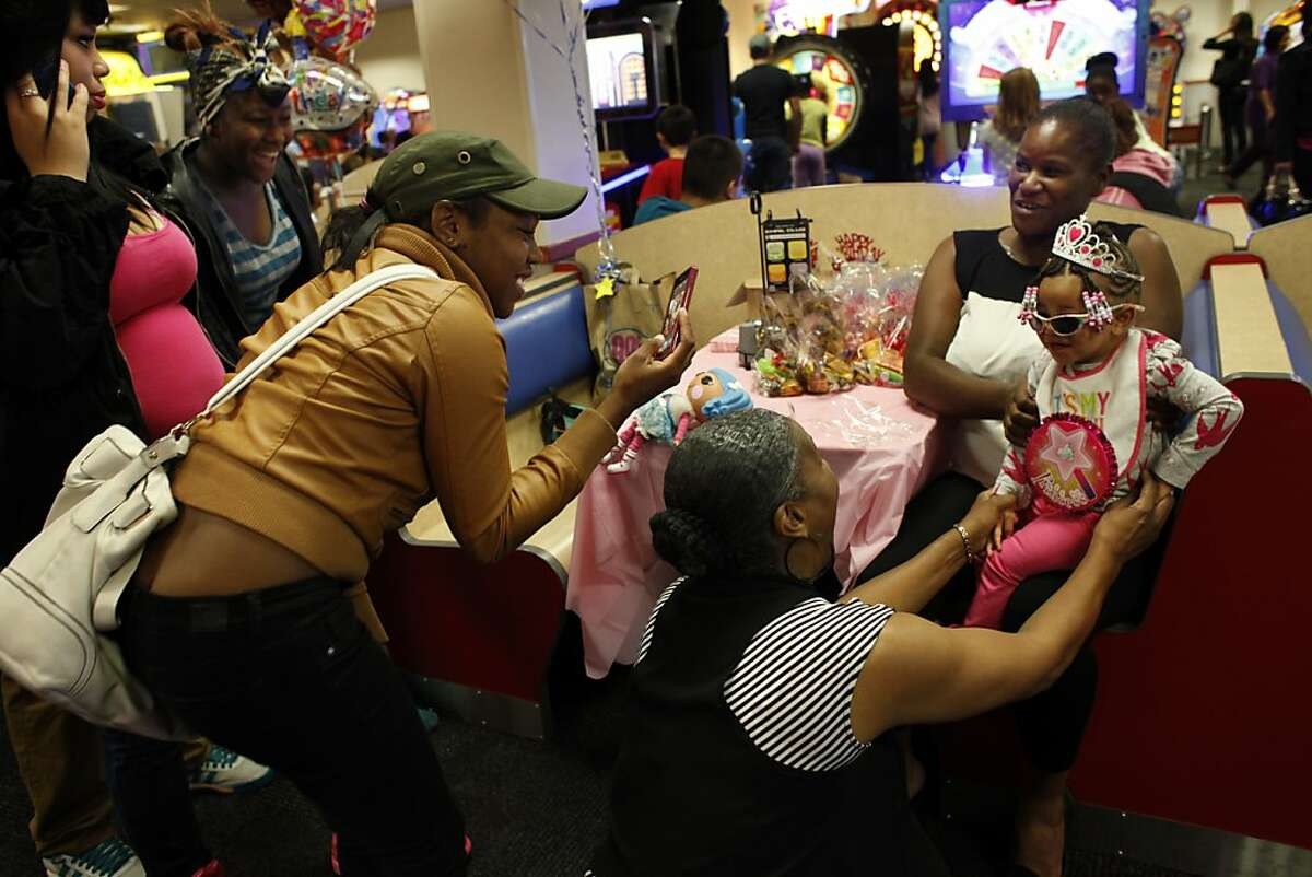 Brijjanna Price, left, tries to get in touch with her father while other family members take LaMya Deshana's picture as the birthday princess for her first birthday party at Chuck E. Cheese's, Saturday, November 9, 2013, in Hayward, Calif. Photo: Lacy Atkins, The Chronicle