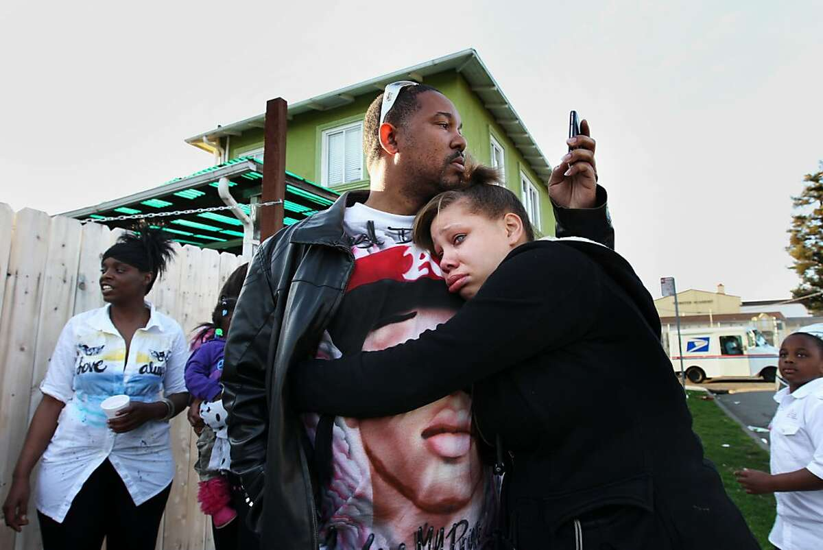 Brijjanna Price, 17, seeks comfort  from her father Ramon Price Sr. during the vigil marking the one year anniversary of her brother Lamont's killing, Saturday February 16, 2013, in Oakland, Calif. Lamont Price, 17, was one of the 131 homicides in 2012. Photo: Lacy Atkins, The Chronicle