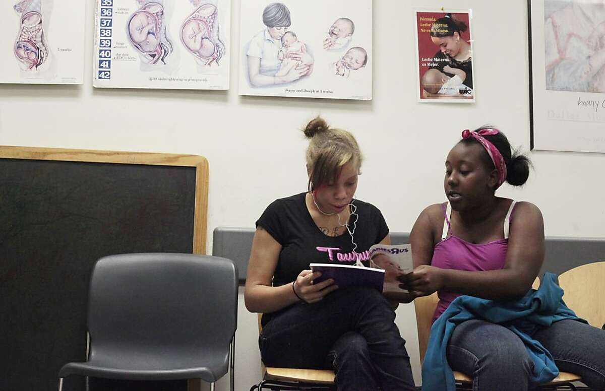 Brijjanna Price, left, looks through the Babies-R-US magazine with stepsister Jeurne  as she waits for the WIC counselor, Tuesday,  May 22, 2012, at the Pittsburgh Health Center in Pittsburgh, Calif. The Women, Infants & Children (WIC) nutrition program provides services to pregnant and postpartum women to stay healthy during their pregnancy. Photo: Lacy Atkins, The Chronicle