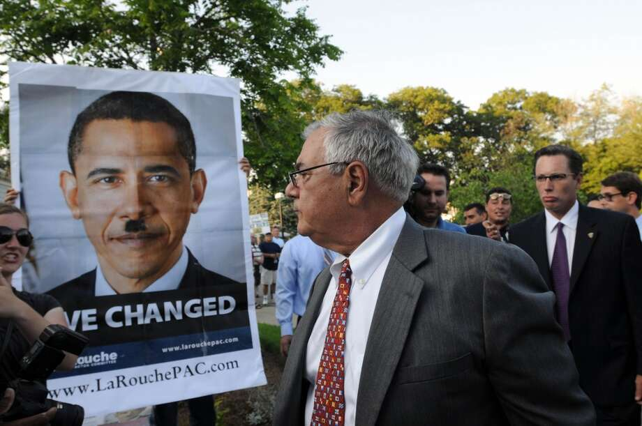 Then-Rep. Barney Frank, D-Mass., reacts to a sign on Aug. 18, 2009. Obama-Hitler posters and photos are occasionally seen being held up by some protesters in the U.S. and around the world. Keep clicking to see other comparisons made between the two. Photo: Darren McCollester, Getty Images