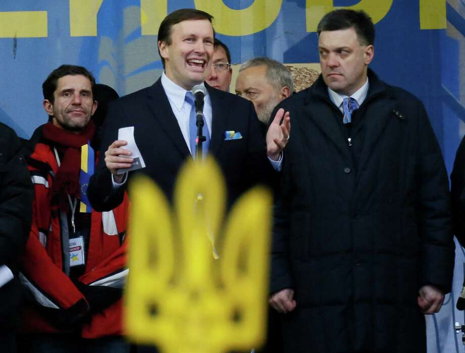 Democratic senator from the state of Connecticut Chris Murphy, left, speaks as opposition leader Oleh Tyahnybok, right, looks at him during a pro-European Union rally in Independence Square in Kiev, Ukraine, Sunday, Dec. 15, 2013. The Ukrainian national symbol is in the foreground. About 200,000 anti-government demonstrators converged on the central square of Ukraine's capital Sunday, a dramatic demonstration that the opposition's morale remains strong after nearly four weeks of daily protests. Photo: Dmitry Lovetsky, AP Photo/Dmitry Lovetsky / Associated Press