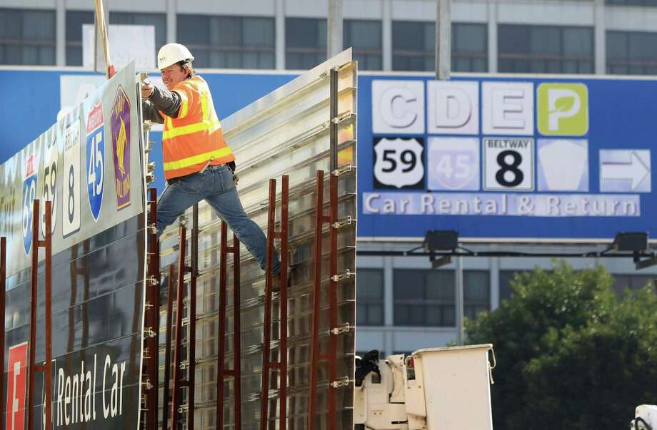 Celestino Velasquez secures the new terminal and highway sign before it is set in place at Bush Intercontinental Airport. Photo: Mayra Beltran, Staff / © 2013 Houston Chronicle