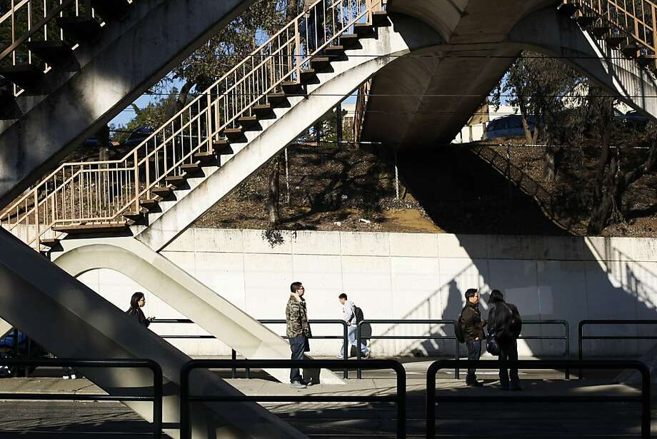 People wait under a pedestrian bridge on Ocean Avenue for inbound KT-Ingleside/Third Street Muni trains. Photo: Pete Kiehart, The Chronicle