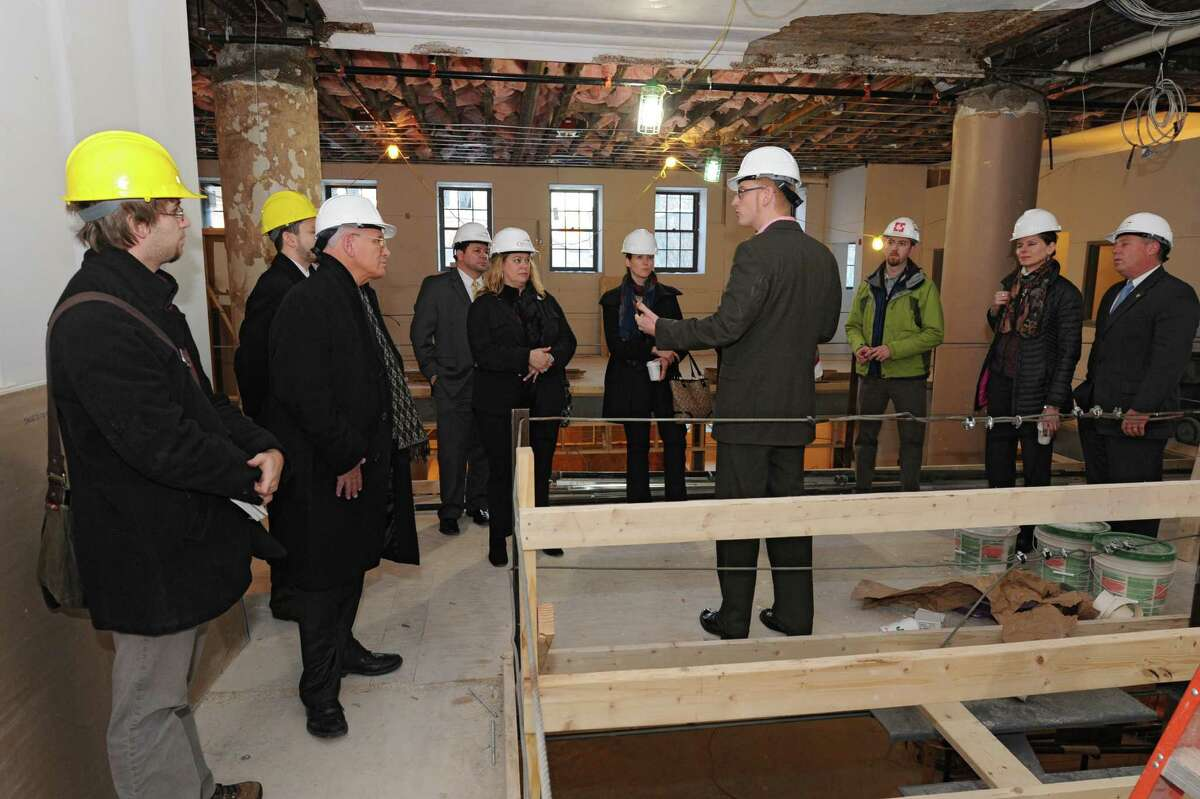 Jeff Mirel, founder and president of the Albany Barn, fourth from right, speaks during a guided tour of the new OThe Barn/Academy Lofts,O formerly St. JosephOs Academy, located in Arbor Hill on Monday, Dec. 16, 2013 in Albany, N.Y. The tour of this artist space was hosted by State Farm and Albany Barn. Invited guest included Congressman Paul Tonko, second from left, Assemblyman John McDonald, right, and Assemblywoman Patricia Fahy, second from right. (Lori Van Buren / Times Union)