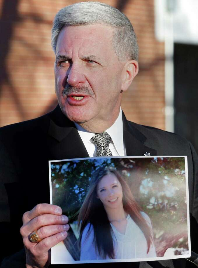 Arapahoe County Sheriff Grayson Robinson holds a picture of Claire Davis, the Arapahoe High student who was shot Friday. A former student, left, prays at a makeshift memorial for the teen. Photo: Ed Andrieski, STF / AP