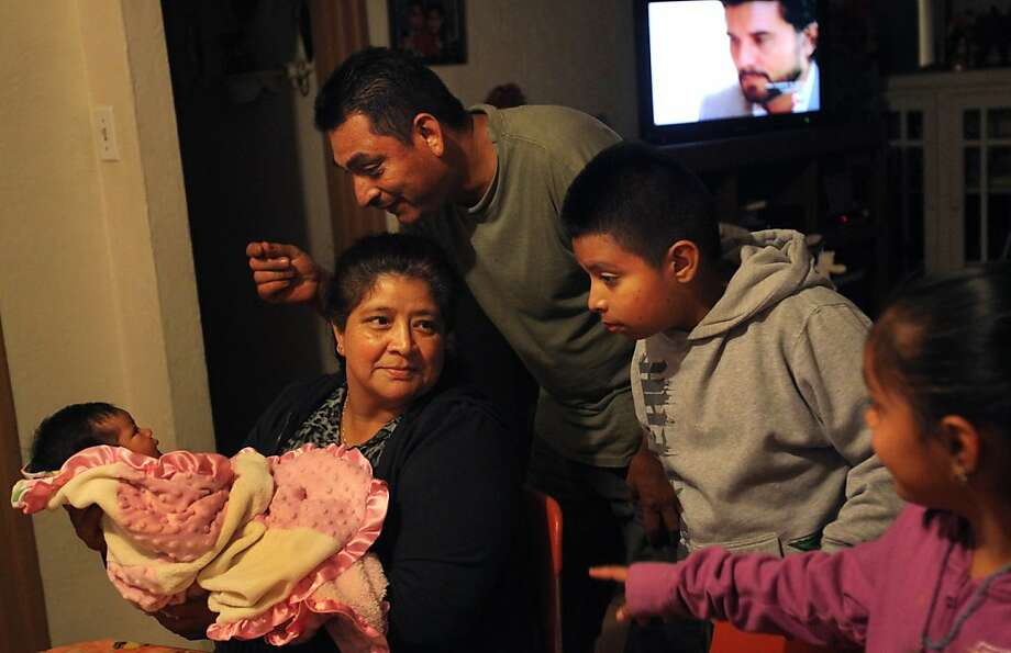 Valeria Castallanos (left) is doted on by grandmother Virginia Arredondo, dad Antonio, brother Rodrigo, 9, and sister Yiselle, 7, after Thanksgiving dinner. Photo: Leah Millis, The Chronicle