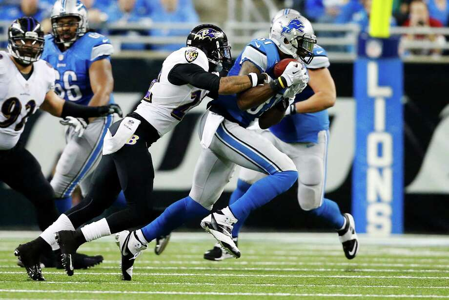 Detroit Lions wide receiver Calvin Johnson, right, is stopped by Baltimore Ravens cornerback Jimmy Smith after a 7-yard reception during the second quarter of an NFL football game in Detroit, Monday, Dec. 16, 2013. With the catch, Johnson becomes the first player in NFL history to record 5,000 yards in any three-season span. (AP Photo/Rick Osentoski) ORG XMIT: DTF110 Photo: Rick Osentoski / FR170444 AP