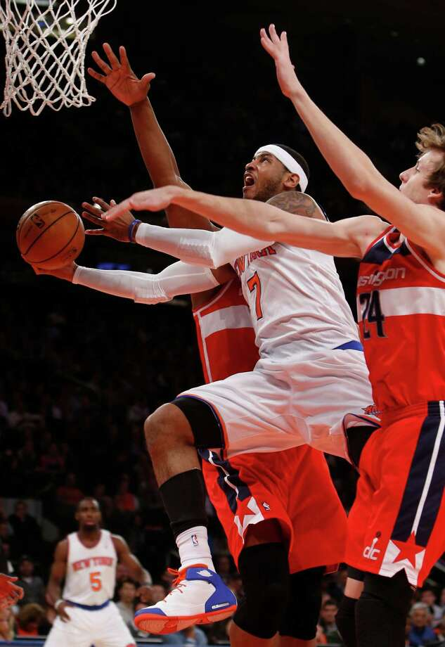 New York Knicks' Carmelo Anthony (7) goes to the basket against a double team from Washington Wizards' Kevin Seraphin, behind, of France, and Jan Vesely (24), of the Czech Republic, during the first half of an NBA basketball game Monday, Dec. 16, 2013, in New York. (AP Photo/Jason DeCrow)   ORG XMIT: NYJD101 Photo: Jason DeCrow / FR103966 AP