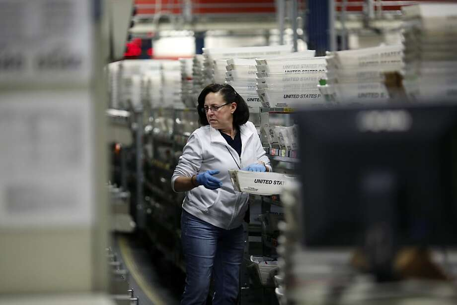 SAN FRANCISCO, CA - DECEMBER 16: An United States Postal Office employee carries a bin of mail at the Processing and Distribution Center on December 16, 2013  in San Francisco, California. An estimated 6 million customers are expected to visit post offices nationwide on what the Postal Service anticipates to be the busiest day of the holiday season as they predict to process 607 million pieces of mail, up from the average 545 million pieces.(Photo by Stephen Lam/Getty Images) Photo: Stephen Lam, Getty Images