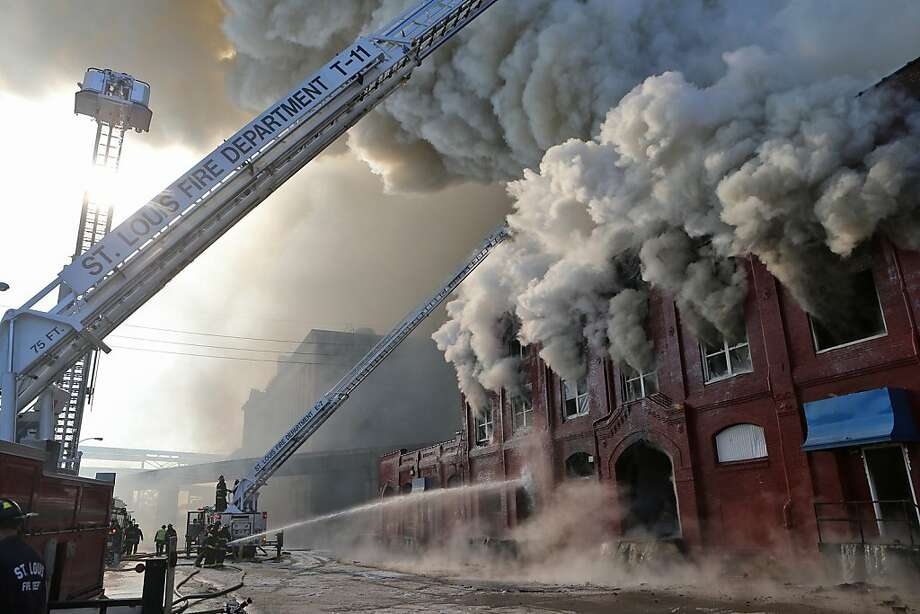 After breaking down the doors of a warehouse at 709 S. First Street, St. Louis firefighters had to retreat because of the intense heat and flame coming from the building in the warehouse district near the St. Louis riverfront on Monday, Dec. 16, 2013. Over 80 firefighters were called to the scene. No one was injured. (AP Photo/The St. Louis Post-Dispatch, J.B. Forbes) Photo: J.B. Forbes, Associated Press