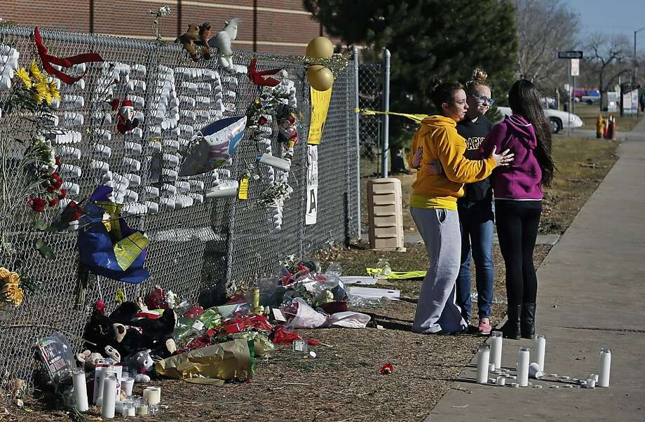 Arapahoe High School students hug after leaving items at a makeshift tribute site three days after a shooting attack at the school in Centennial, Colo., Monday, Dec. 16, 2013. They are, left to right, Hannah Eddy, Gavyn Bills, and Vania Arevalo. During the attack, the shooter shot a classmate in the head at close range with a shotgun, before killing himself. (AP Photo/Brennan Linsley) Photo: Brennan Linsley, Associated Press