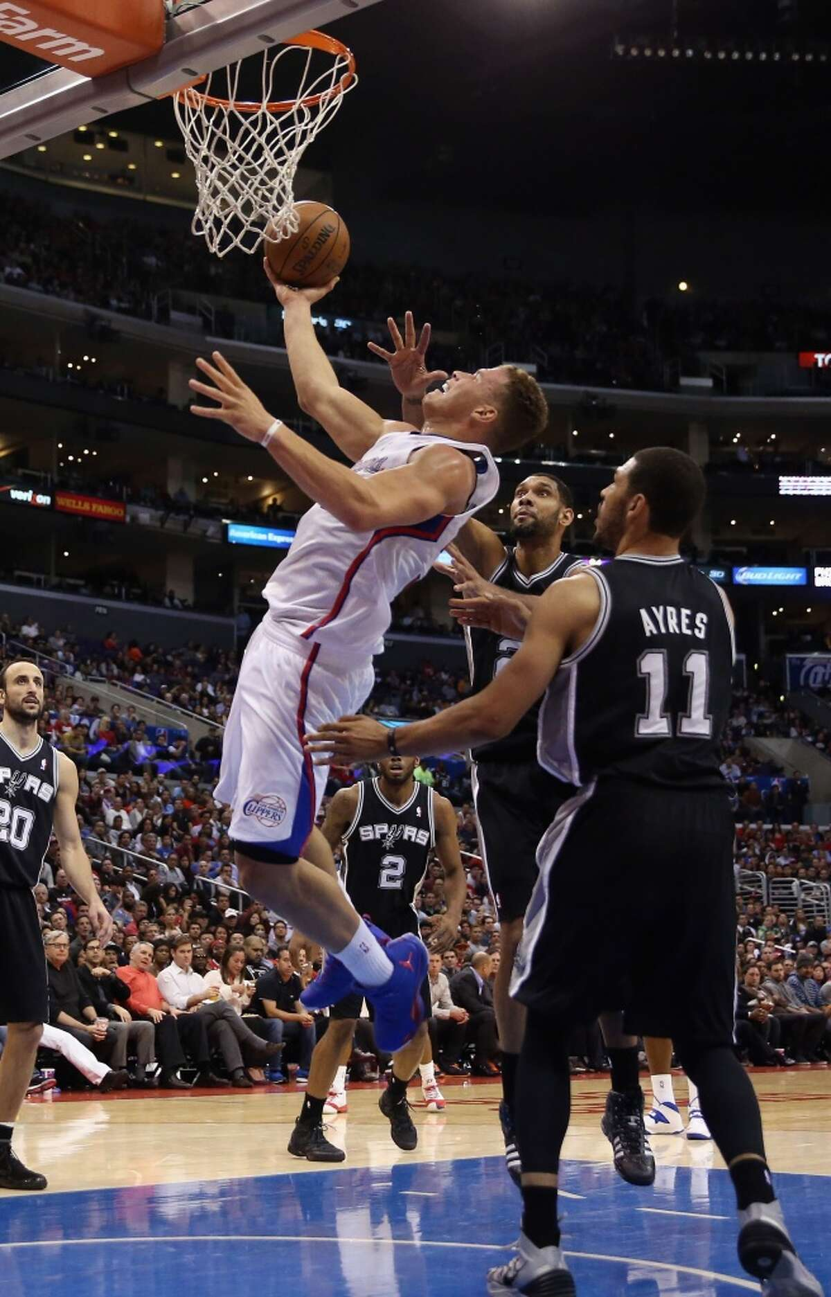 Blake Griffin #32 of the Los Angeles Clippers drives to the basket past between Tim Duncan #21 and Jeff Ayres #11 of the San Antonio Spurs in the first half at Staples Center on December 16, 2013 in Los Angeles, California.