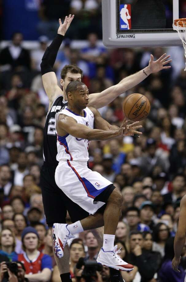 Los Angeles Clippers' Willie Green, front, passes the ball as he is defended by San Antonio Spurs' Tiago Splitter, of Brazil, during the first half of an NBA basketball game on Monday, Dec. 16, 2013, in Los Angeles. Photo: Jae C. Hong, Associated Press
