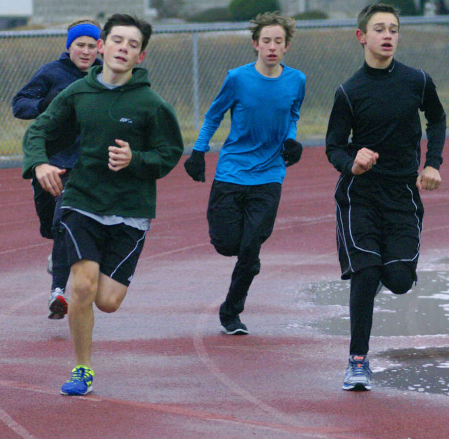 Green Wave athletes, from left to right, front, Kurt Jonke and Hunter Barron, and, back, Evan Brofford and William Ginn, get in a good workout Dec. 9 during New Milford High School boys' indoor track practice.  Dec. 9, 2013 Photo: Norm Cummings / The News-Times