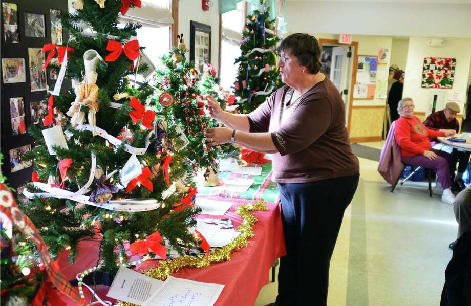 Event chairwoman Donna Walker arranges Christmas trees decorated for the Festival of Trees at the Rensselaer County Everett Wagar Senior Center in Grafton, N.Y. More than two dozen trees adorned the center for an event in early December. (John Carl D'Annibale / Times Union) Photo: John Carl D'Annibale / 00024894A