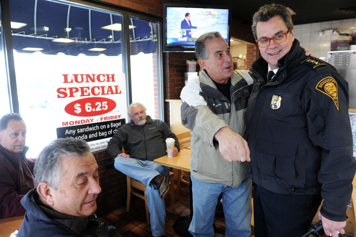 Pete Minaya, of Bridgeport, shows Police Chief Joseph Gaudett the spot where a Bridgeport Police Officer was sitting when he accidently shot himself during breakfast at the Bagel King on upper Main St., in Bridgeport, Conn., Dec. 17, 2013.