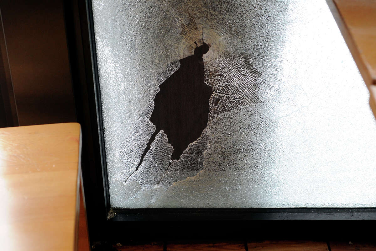 A bullet hole and shattered window where a Bridgeport Police Officer accidently shot himself during breakfast at the Bagel King on upper Main St., in Bridgeport, Conn., Dec. 17, 2013.