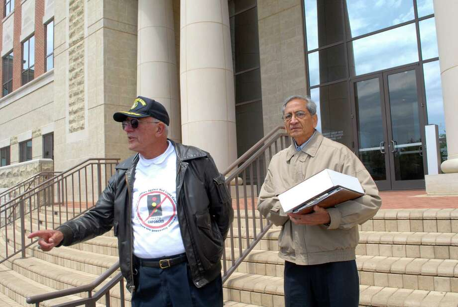 Helwig Van Der Grinten, left, and Ray Patel stood on the steps of Sugar Land City Hall last spring to talk about the city's red light camera program. Photo: George Wong / Freelance