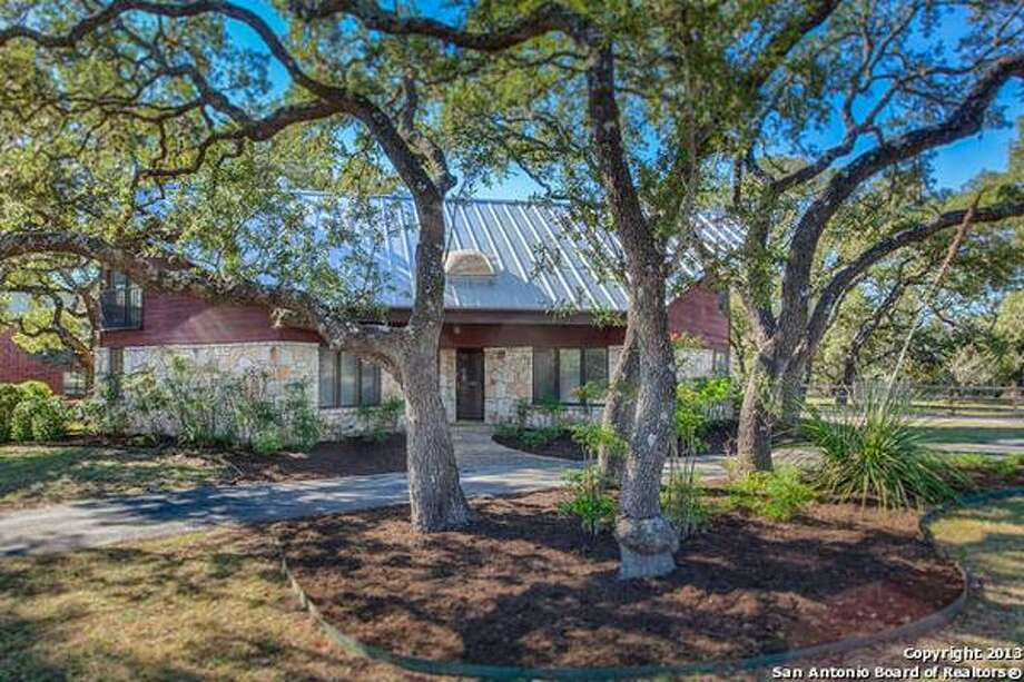 Tree-studded one acre lot highlights this inviting home with stone exterior, metal roof and circular drive. 4 Bedrooms, 2 Full Baths, 1 Partial Baths, 3,082 Sq Ft, MLS: 1030085 Photo: Courtesy
