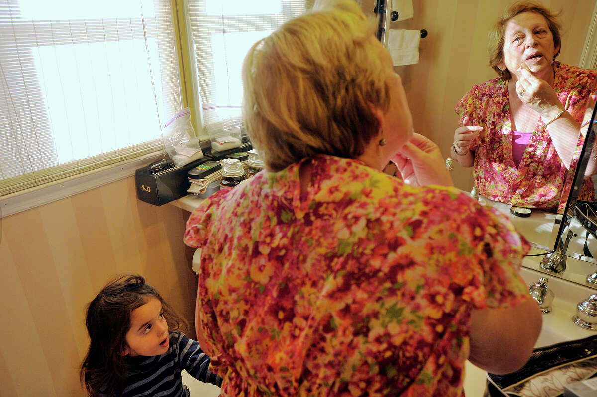 Three-year-old Chetana Sandhu, bottom left, watches as her grandmother, Lorraine Kweskin, puts on makeup before demonstrating how she plays Nurse Morning Glory, a clown character, at her home in Stamford, Conn., on Monday, Nov. 25, 2013. Kweskin is a volunteer with The HAHA Clowns at Stamford Hospital. HAHA stands for Health And Humor Associates.