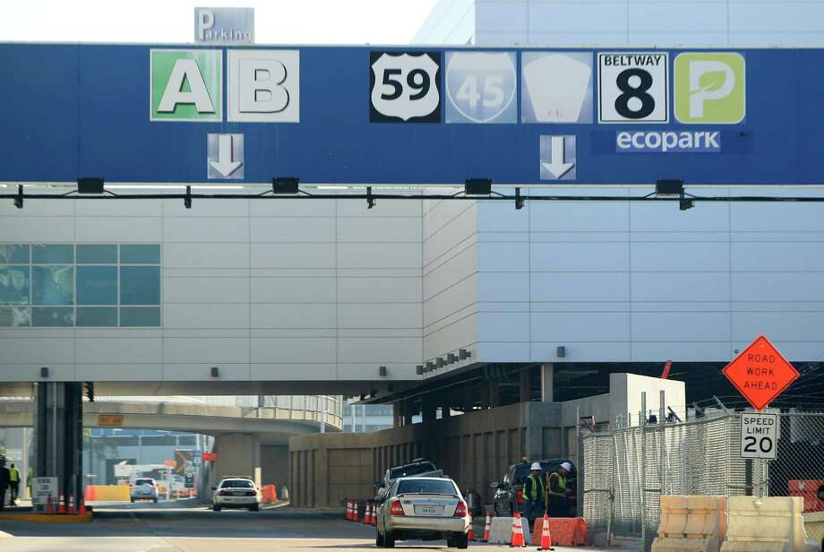 Faded highway and terminal signs are replaced by workers at Bush Intercontinental Airport on Monday, Dec. 16, 2013, in Houston. ( Mayra Beltran / Houston Chronicle )? Photo: Mayra Beltran, Houston Chronicle / © 2013 Houston Chronicle