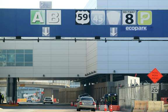 Faded highway and terminal signs are replaced by workers at Bush Intercontinental Airport on Monday, Dec. 16, 2013, in Houston. ( Mayra Beltran / Houston Chronicle )?