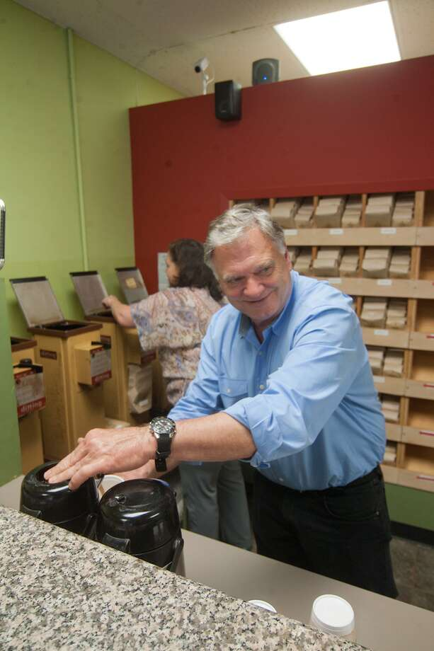 Mike Mulloy pulls a sample for a customer at House of Coffee Beans, which  celebrated its 40th anniversary in August. Photo: R. Clayton McKee, Freelance / © R. Clayton McKee